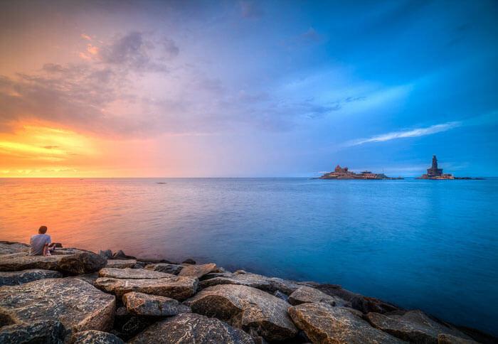 A lone traveler enjoys the magnificent sunrise at the Kanyakumari Beach