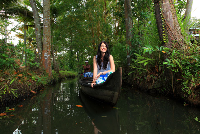 A young woman takes a canoe ride in the backwaters of Alleppey