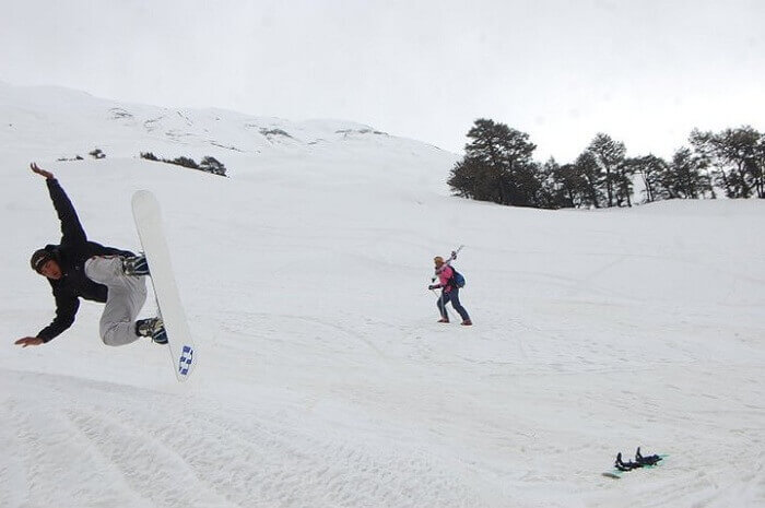 A tourist shows stunt with snowboard near Rohtang pass